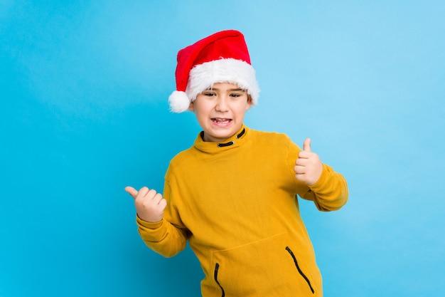 Weinig jongen het vieren kerstmisdag die een santahoed draagt isoleerde omhoog opheffend beide duimen, glimlachend en zeker.