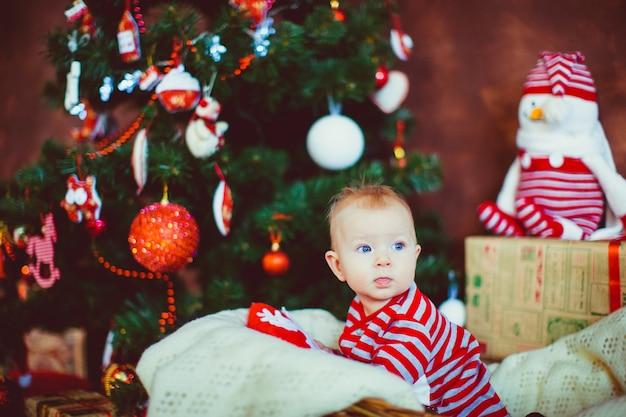 Weinig jongen in gestripte pyjama zit vóór een kerstboom