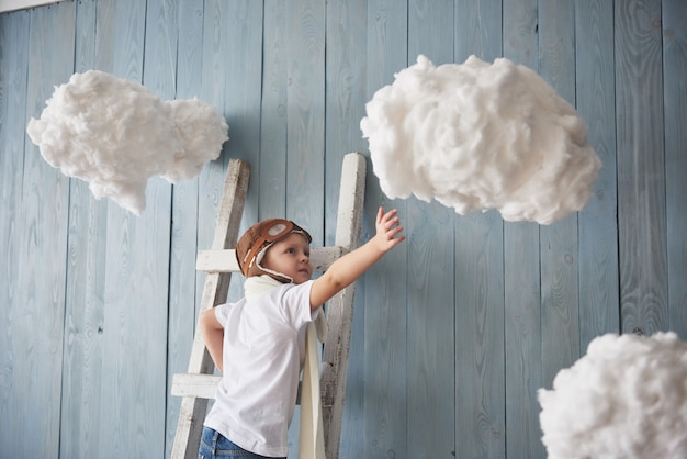 Weinig jongen in proefhoed die zich op de ladder in bevinden. reik naar de hemel. raak de wolken aan