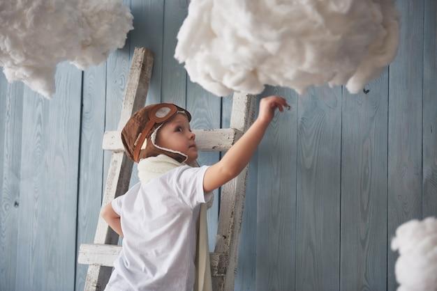 Weinig jongen in proefhoed die zich op de ladder in de studio bevindt. reik naar de hemel. raak het wolkenconcept aan