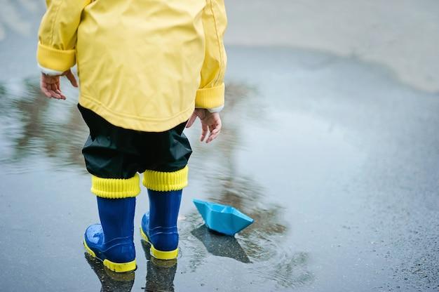 Weinig jongen in regenjas en rubberlaarzen die in vulklei spelen. gelukkig klein kind met papieren schip