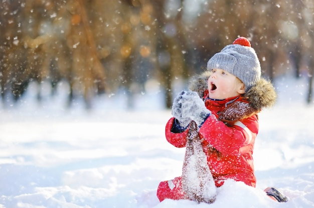 Weinig jongen in rode de winterkleren die pret met sneeuw hebben