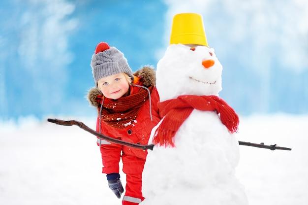 Weinig jongen in rode de winterkleren die pret met sneeuwman in sneeuwpark hebben
