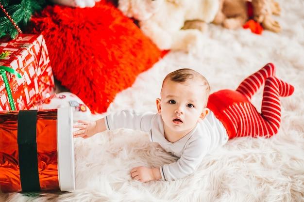 Weinig jongen in rode panty ligt op pluizig tapijt