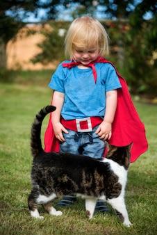 Weinig jongen in superherokostuum met zijn kat in een werf
