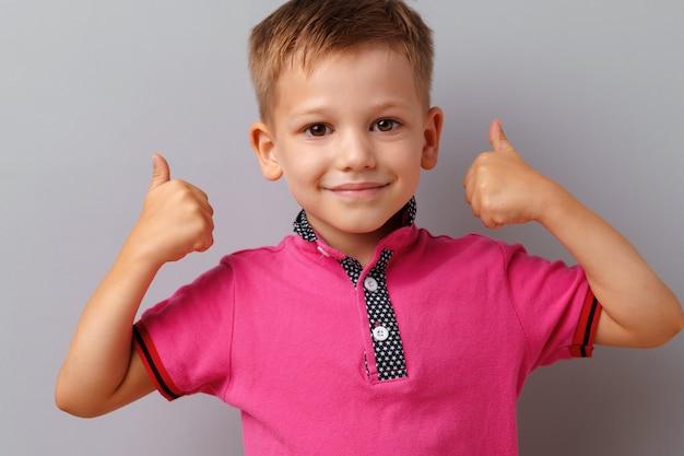 Weinig jongen in t-shirt die duimen tonen ondertekent omhoog over grijze achtergrond