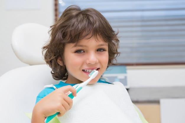Weinig jongen in tandartsen zit met behulp van toothrbrush voor