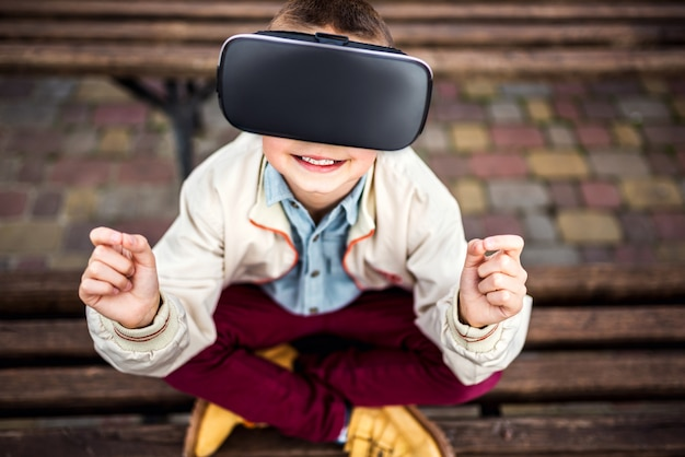 Weinig jongen in virtuele werkelijkheidsglazen in het park