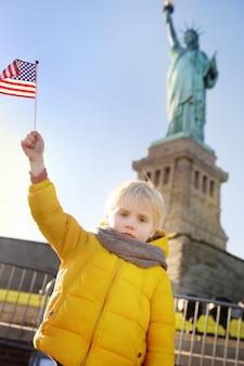 Weinig jongen met amerikaanse vlag op de achtergrond van het standbeeld van vrijheid in dezelfde pose. reis met kinderen.