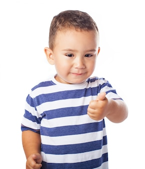 Weinig jongen met een duim omhoog
