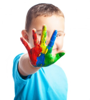 Weinig jongen met een hand vol verf die zijn gezicht