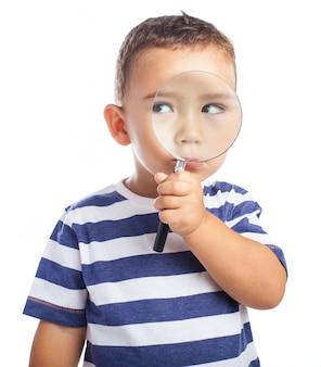 Weinig jongen met een vergrootglas