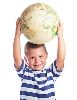 Weinig jongen met een wereldbol op zijn hoofd
