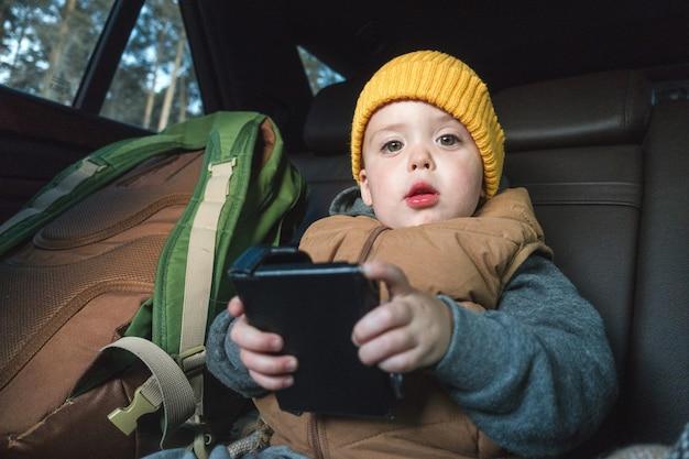 Weinig jongen met gadget in auto
