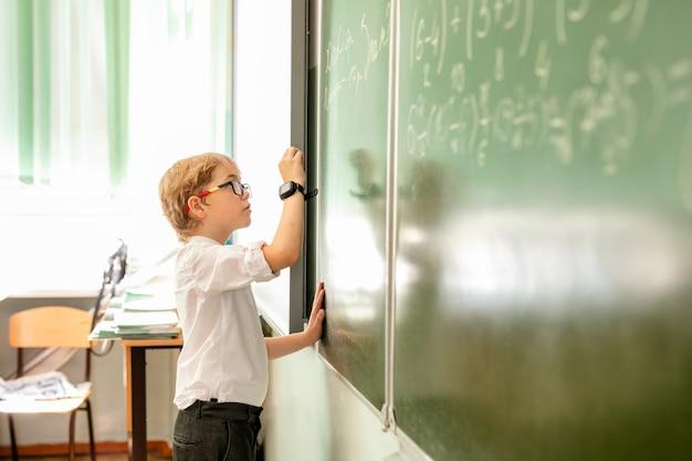 Weinig jongen met grote zwarte glazen en wit overhemd die zich dichtbij schoolbord bevinden met een krijtje die slim het denken gezicht maken