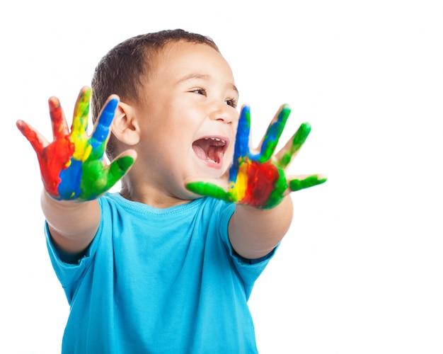 Weinig jongen met handen vol met verf en met open mond