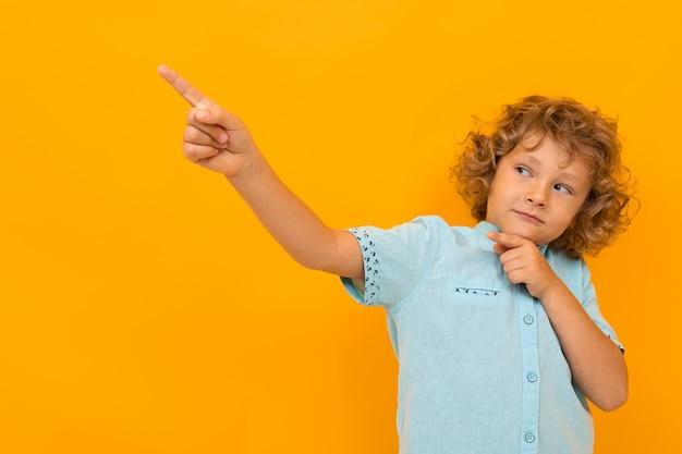 Weinig jongen met krullend haar in blauw overhemd en borrels toont duimen die op gele achtergrond worden geïsoleerd