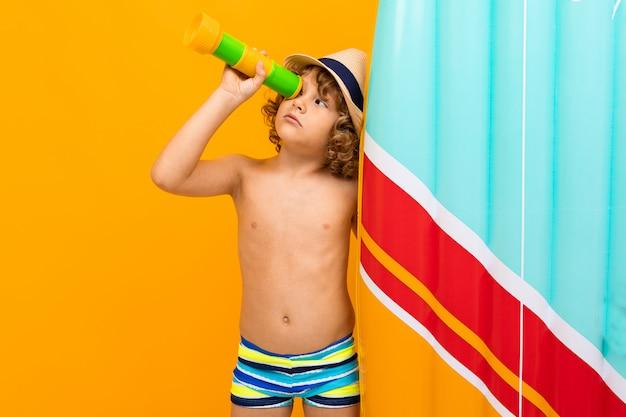 Weinig jongen met krullend haar in zwempak met rubbermatras dat op geel wordt geïsoleerd