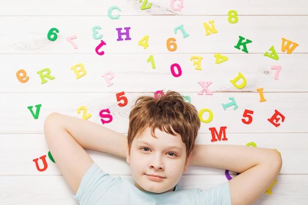 Weinig jongen met regenboogalfabetbrieven die op de houten vloer leggen.