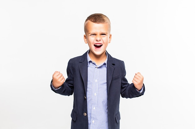 Weinig jongen met winnend gebaar dat op witte muur wordt geïsoleerd