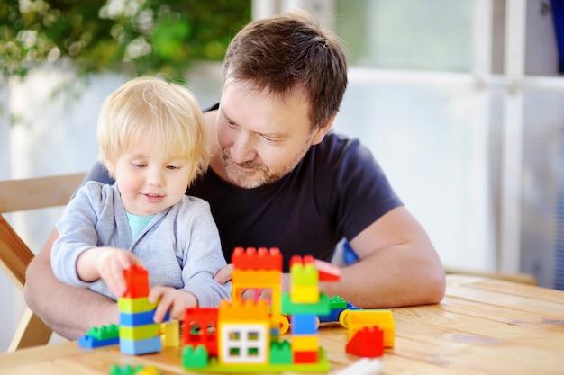Weinig jongen met zijn vader die met kleurrijke plastic blokken thuis spelen