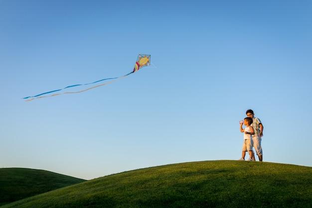 Weinig jongen op de zomervakantie die pret en gelukkige tijd hebben die vlieger op het overzeese strand vliegen