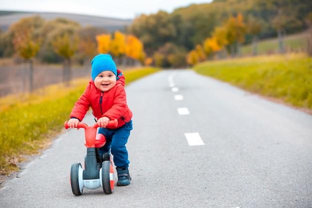 Weinig jongen op een fiets of uitsmijter in openlucht of fietspad, dat gelukkig kijkt