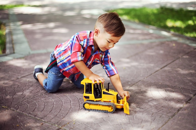 Weinig jongen speelt met speelgoed in het park van de zomer