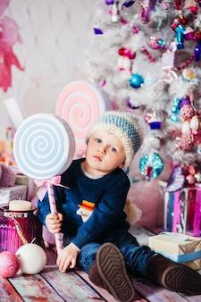 Weinig jongen speelt met speelgoed vóór een witte boom chritmas