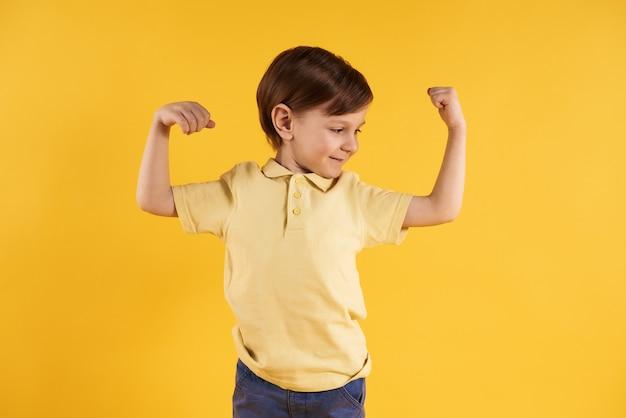 Weinig jongen toont bicepsen op geel worden geïsoleerd dat