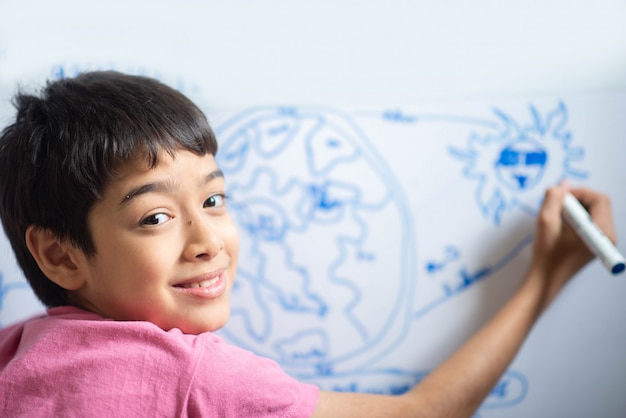 Weinig jongen trekt aarts op het whiteboard in de ruimte