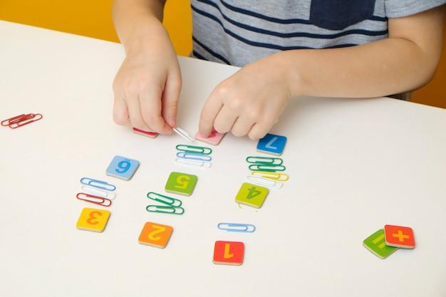 Weinig jongenskind die voor basisschool voorbereidingen treffen die eenvoudige wiskundeoefeningen doen. detailopname
