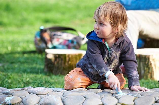 Weinig jongenstekening met stoepkrijt in het park.