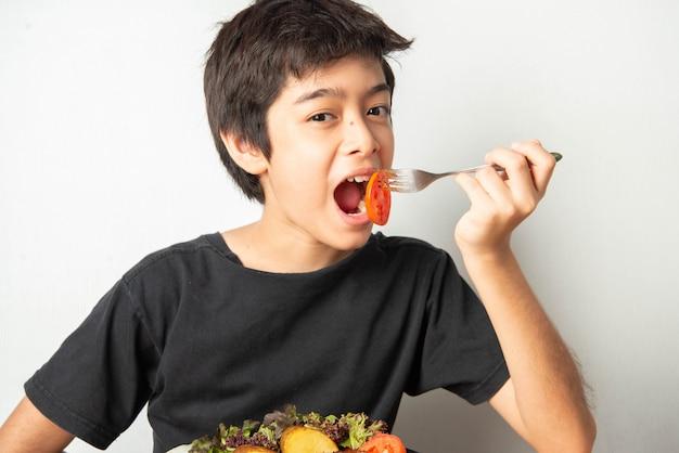 Weinig jongenstiener die tomaat met salade voor zijn maaltijd eet