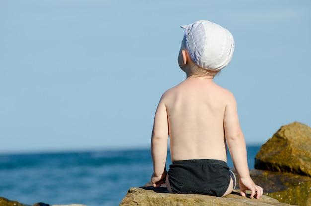 Weinig jongenszitting met van hem terug naar een rots aan de kust in zwembroek, blauwe hemel, ruimte voor tekst
