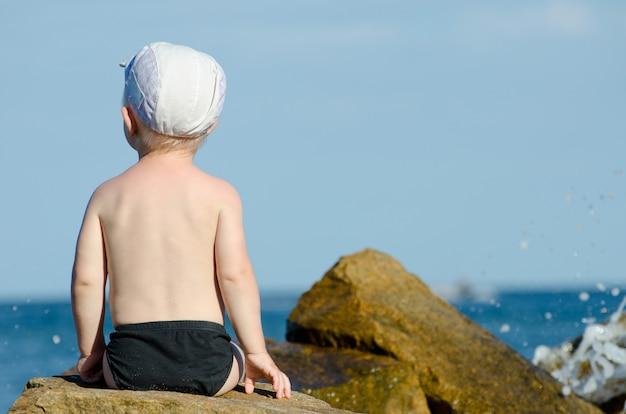 Weinig jongenszitting met van hem terug naar een rots aan de kust in zwembroek, blauwe hemel