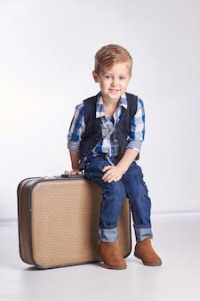 Weinig jongenszitting op koffers, die vakantie voorbereiden