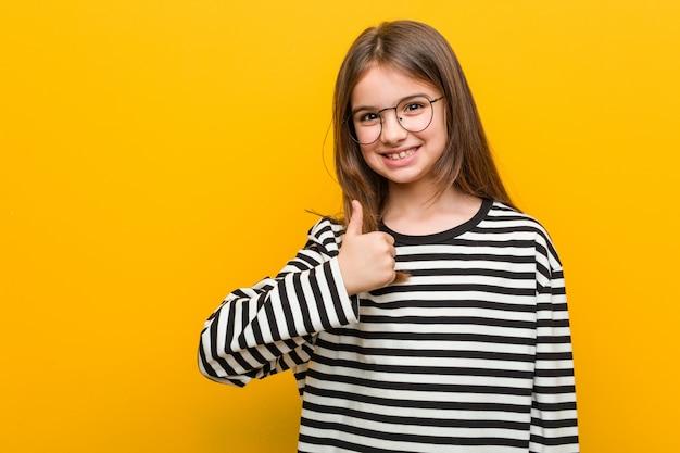 Weinig kaukasisch leuk meisje dat en duim glimlacht opheft