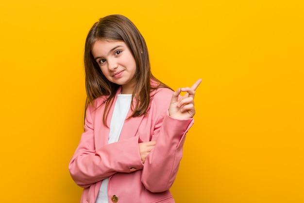 Weinig kaukasisch leuk meisje glimlachen die vrolijk met weg wijsvinger glimlachen.