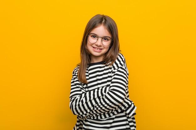 Weinig kaukasisch leuk meisje glimlachend zeker met gekruiste armen.