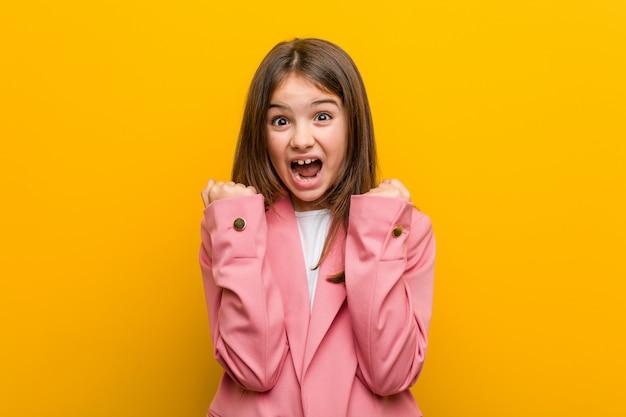 Weinig kaukasisch leuk meisje zorgeloos en opgewekt toejuichen. overwinning concept.
