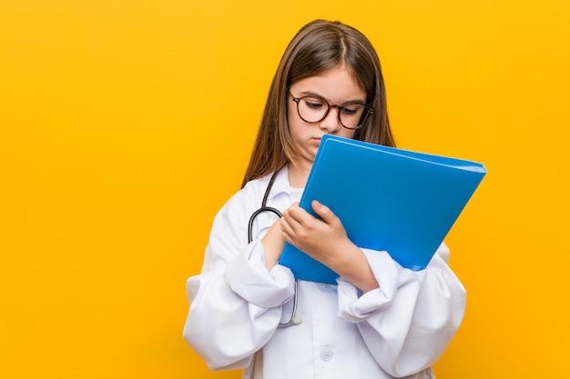 Weinig kaukasisch meisje dat een artsenkostuum draagt