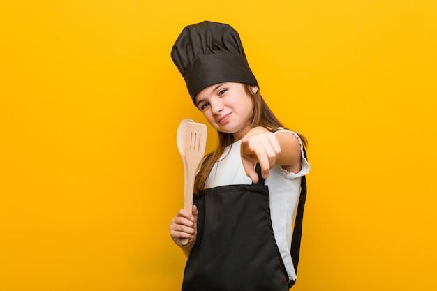 Weinig kaukasisch meisje dat een vrolijke glimlachen van het chef-kokkostuum draagt die aan voorzijde richten.