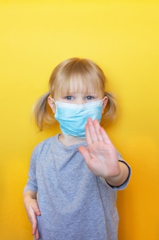 Weinig kaukasisch meisje dat masker draagt tegen coronavirus covid-19