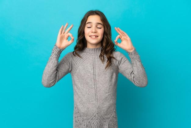 Weinig kaukasisch meisje dat op blauwe achtergrond in zen stelt
