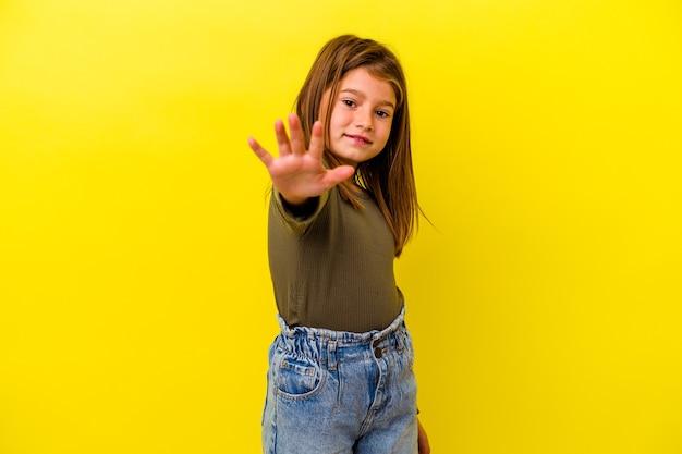 Weinig kaukasisch meisje dat op geel glimlachend vrolijk wordt geïsoleerd dat nummer vijf met vingers toont.