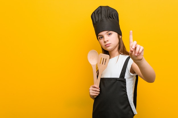 Weinig kaukasisch meisje die een chef-kokkostuum dragen die nummer één met vinger tonen.