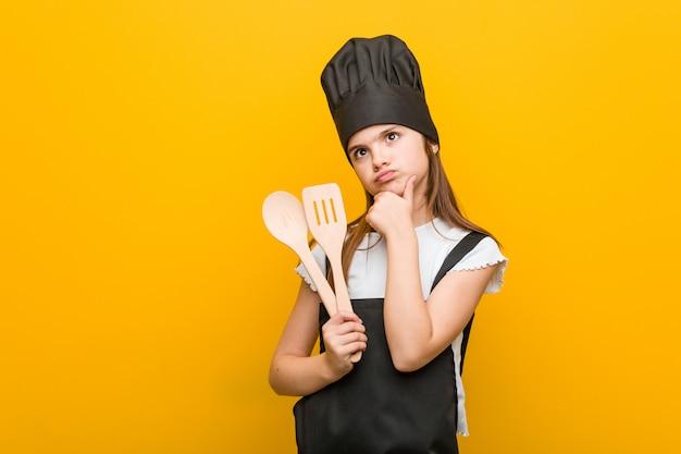 Weinig kaukasisch meisje die een chef-kokkostuum dragen die zijdelings met twijfelachtige en sceptische uitdrukking kijken.
