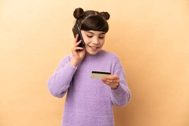 Weinig kaukasisch meisje geïsoleerd kopen met mobiel met een creditcard