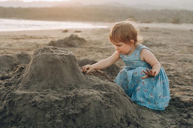 Weinig kaukasisch meisje heeft pret die in het zand bij oceaanstrand graaft, die zandkasteel bouwt